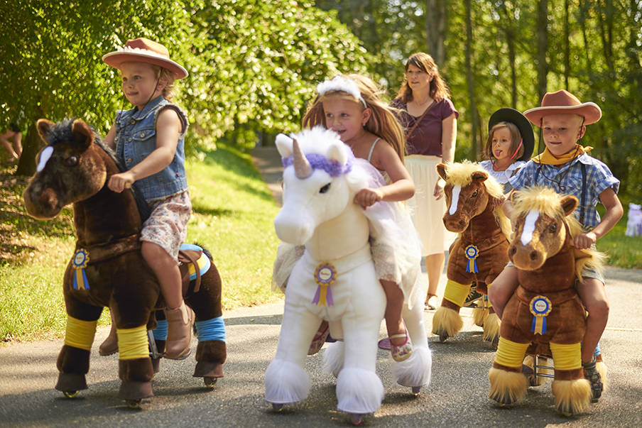 Children learning to ride a unicorn and horses